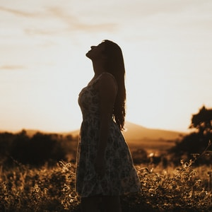 woman wearing floral dress standing on brown grassland