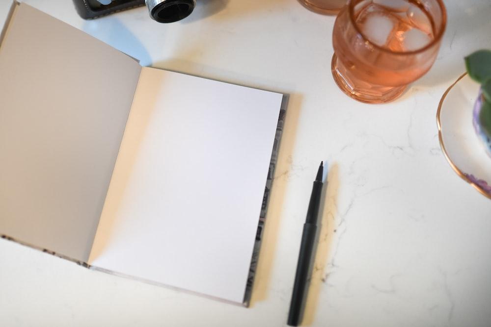 open notebook beside pen