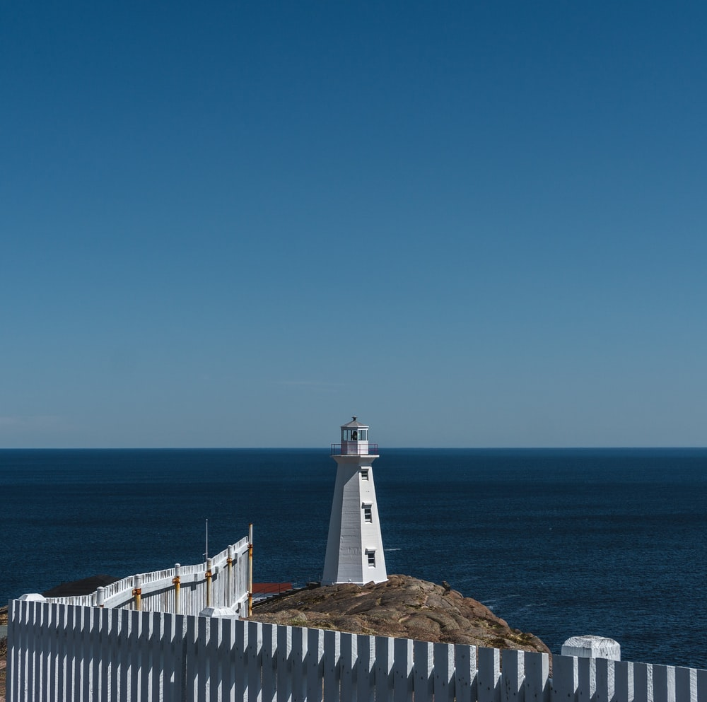 lighthouse on island mountain during day