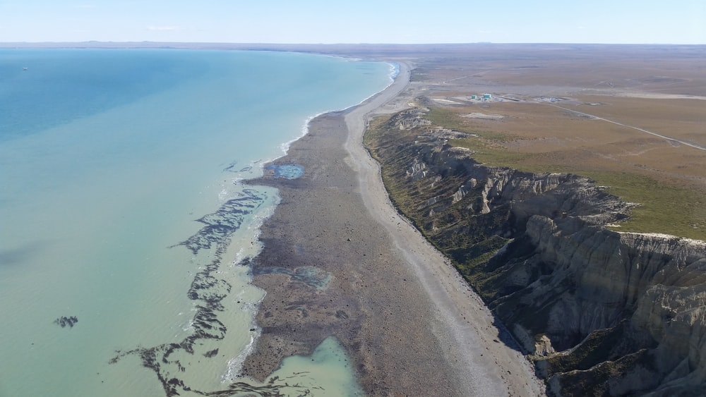 aerial photography of seashore and green field view