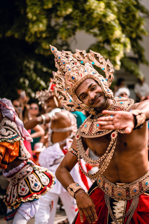 men with golden headdresses dancing on street