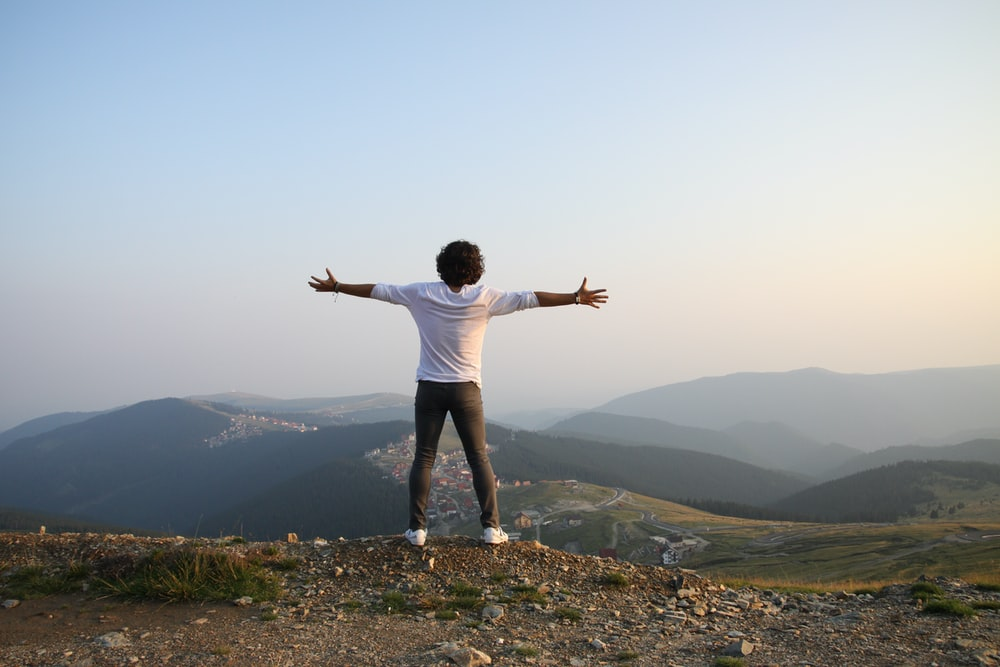 man in white t-shirt and grey pants standing on top of hill