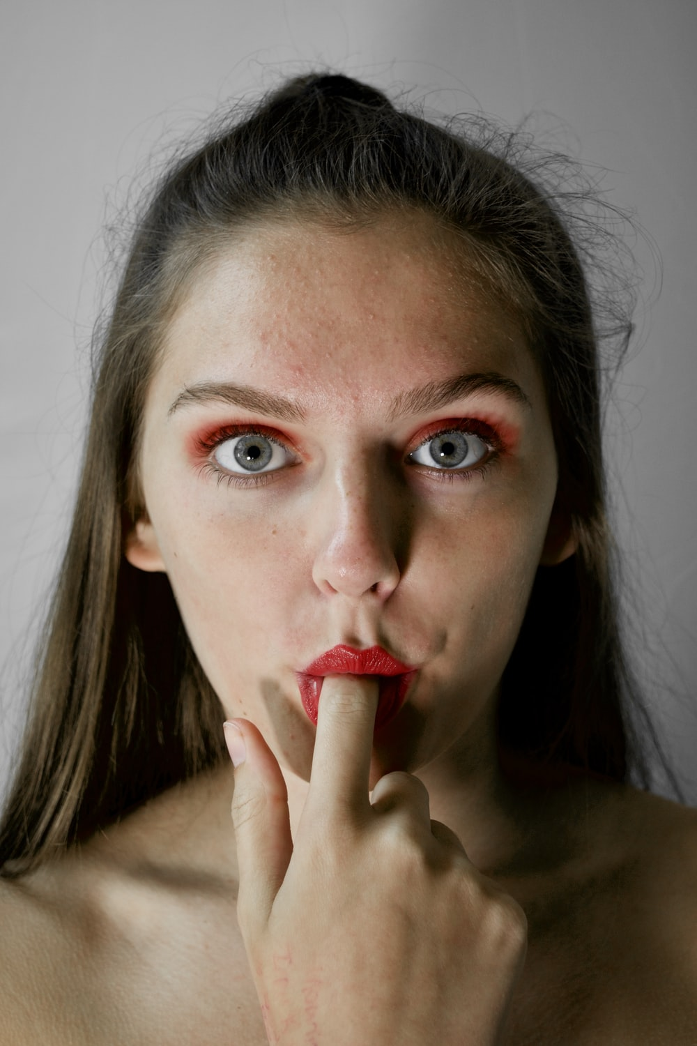 woman with finger on mouth inside room