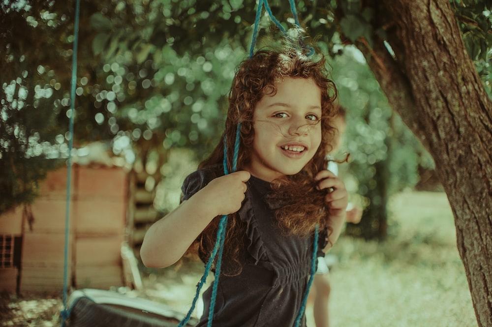 girl standing on swing during daytime
