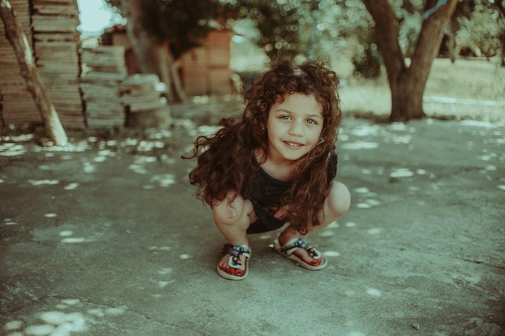 girl squatting near tree during daytime