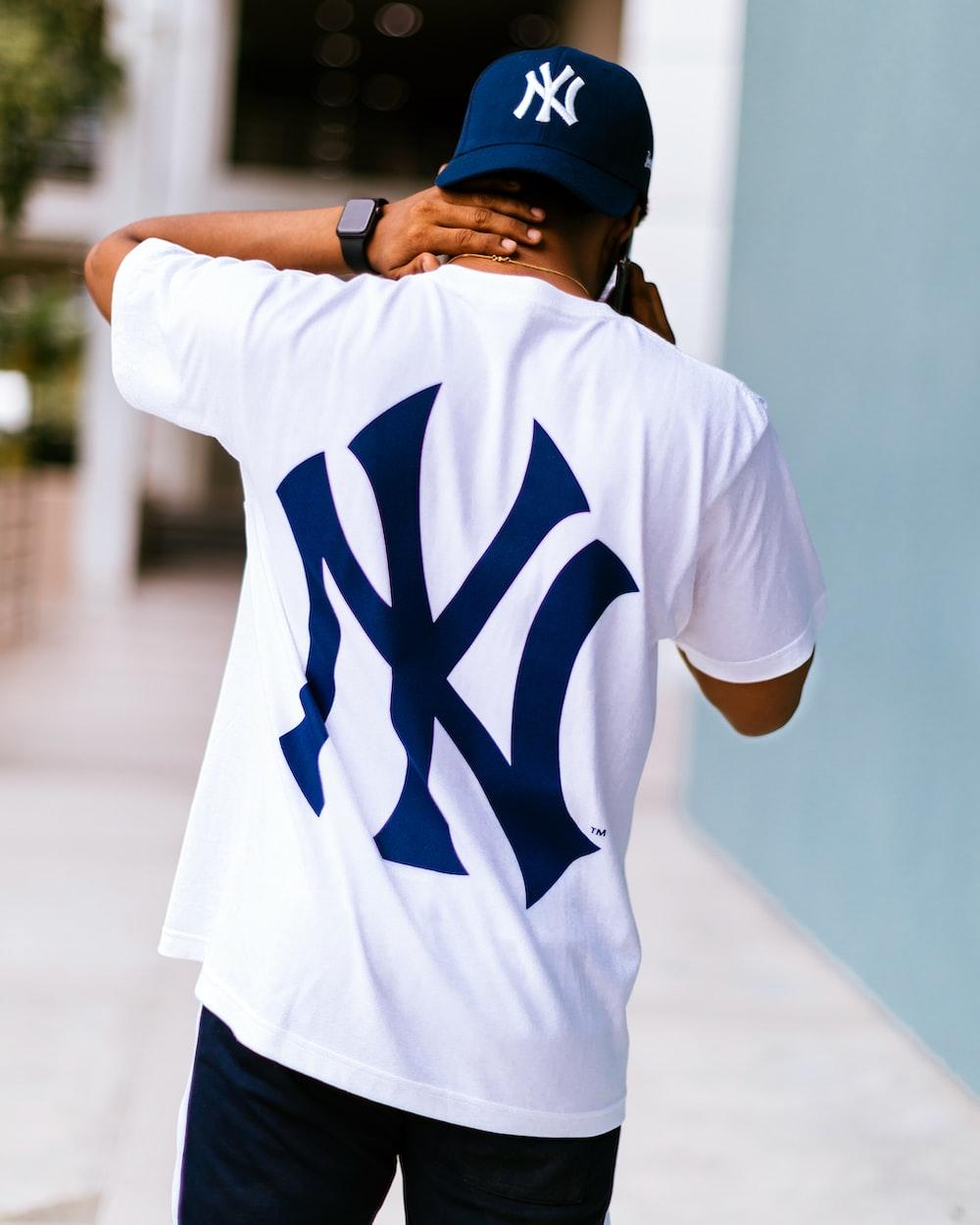 man wearing white and blue New York Yankees t-shirt walking while touching his neck