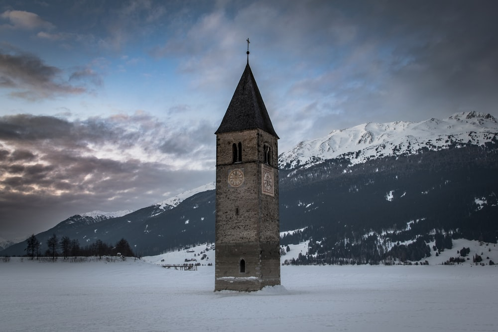 brown and black clock tower jutting out of white snow covered field