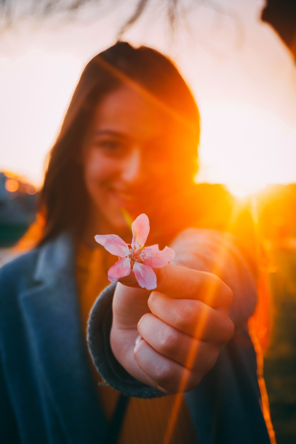 woman holding a pink flower at sunset