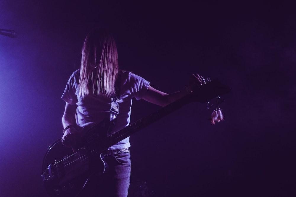woman in white shirt playing electric guitar