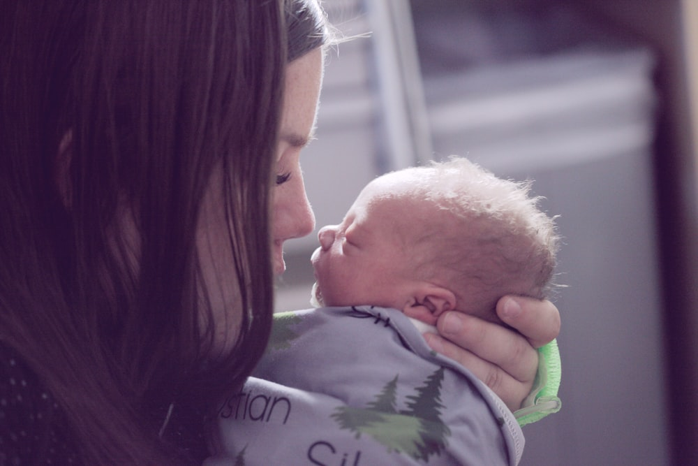 woman kissing baby