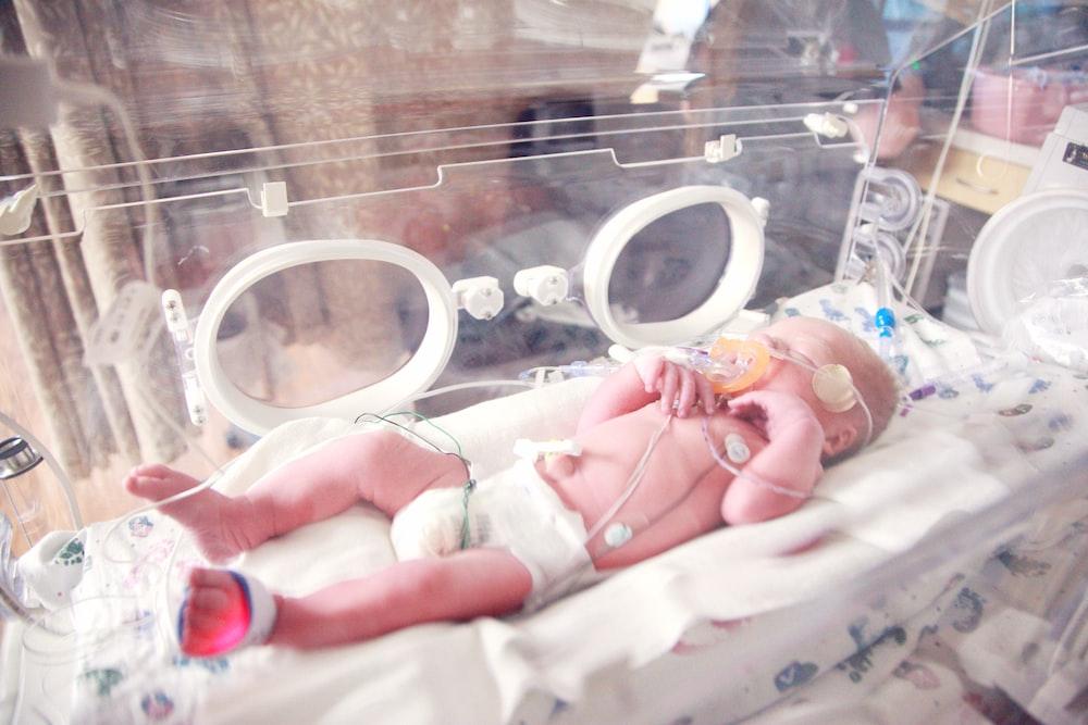baby lying in incubator