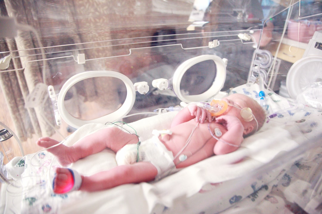 A 34 week premature baby in an isolette incubator with oxygen.