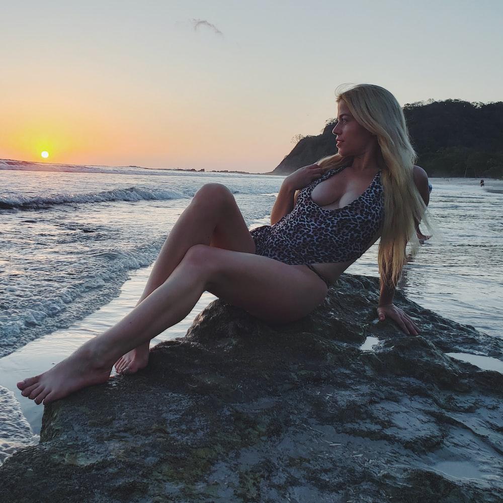 woman wearing black and white bikini sitting on gray rock looking straight on calm sea