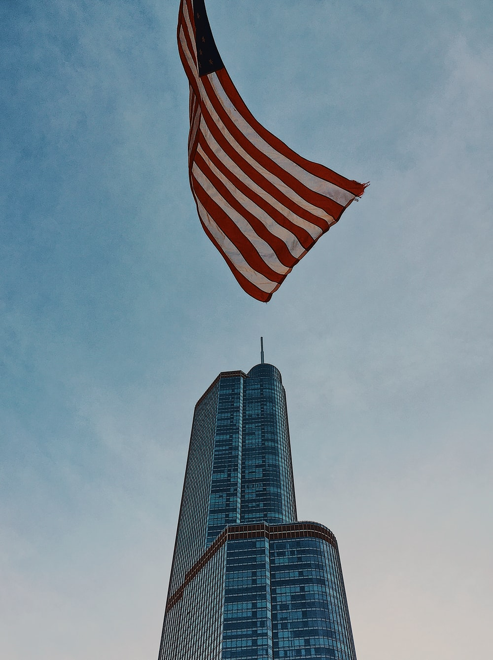 U.S. flag flying n pole in front of blue high rise building