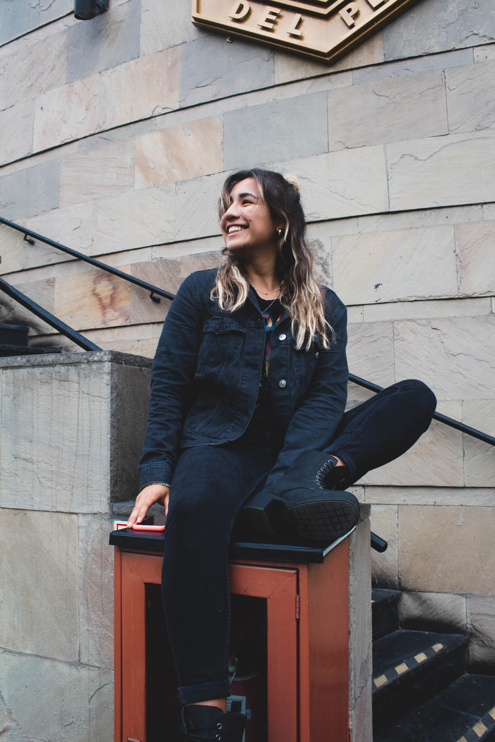 smiling woman in blue jacket and black denim jeans sitting on top of brown wall mounted box