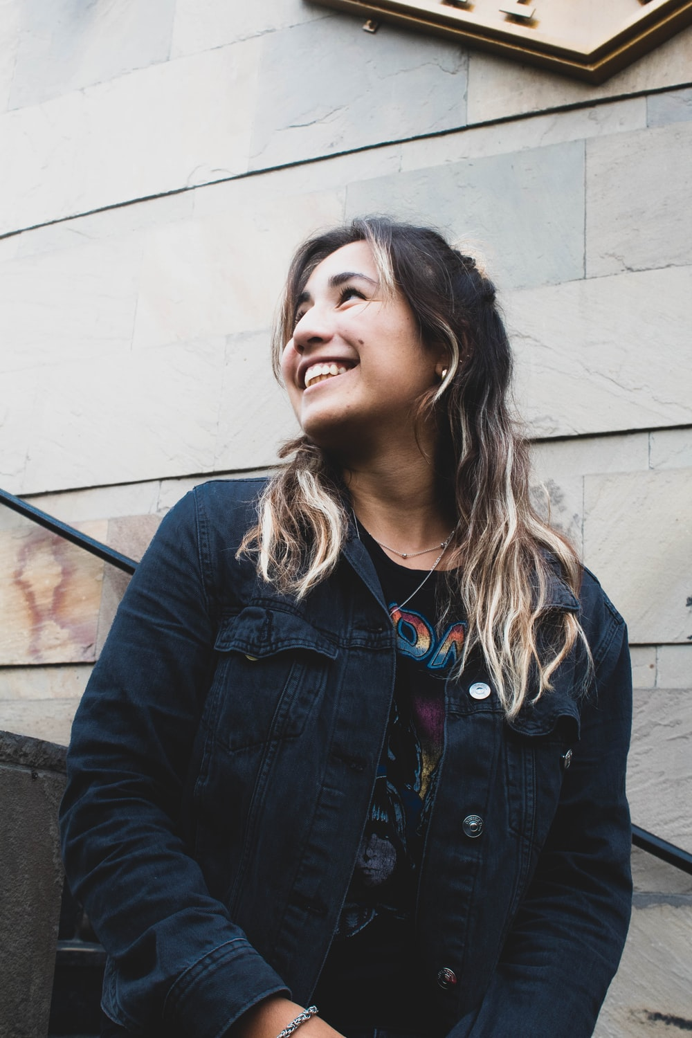 woman in black denim button-up jacket smiling