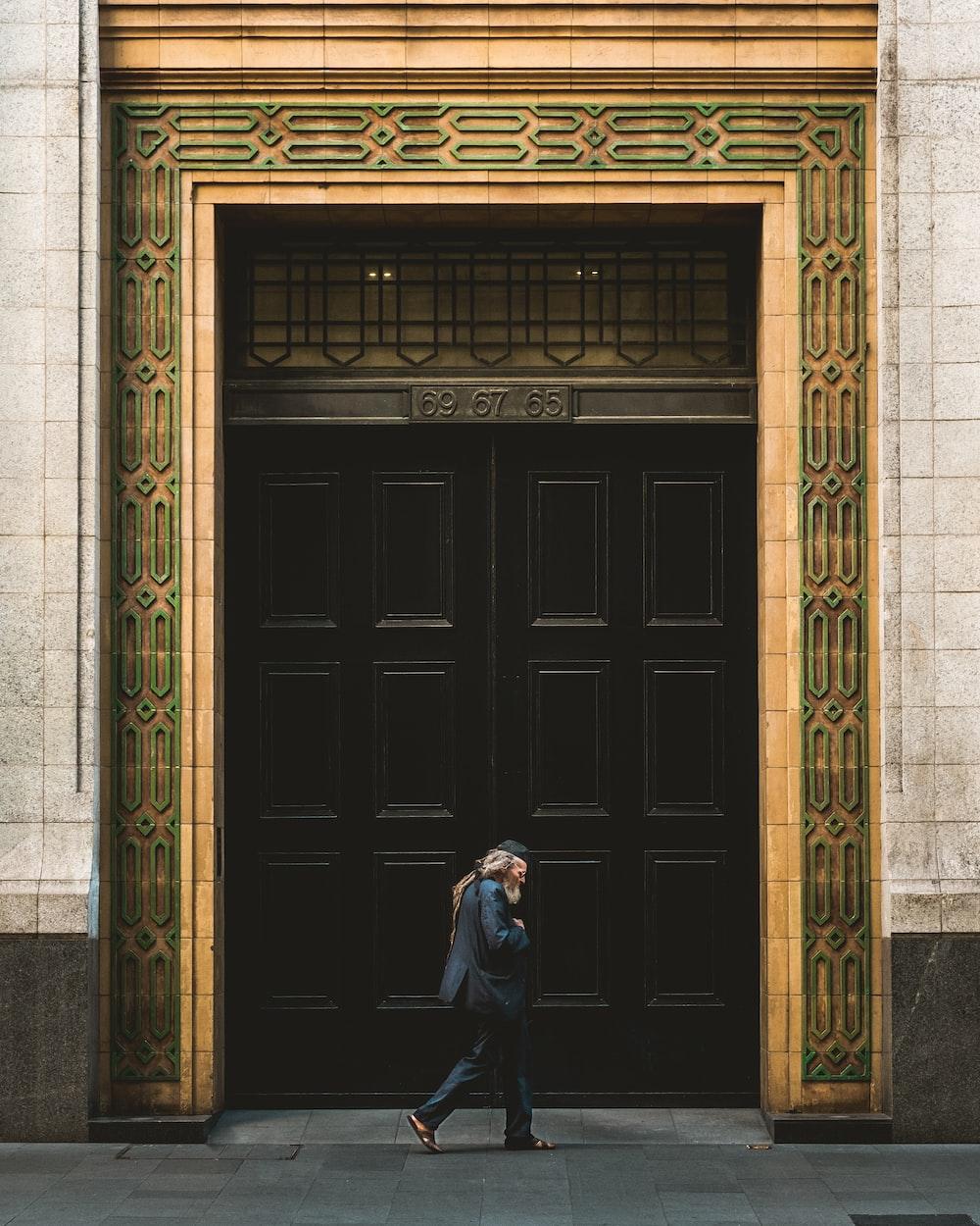 person walking in front of black wooden door