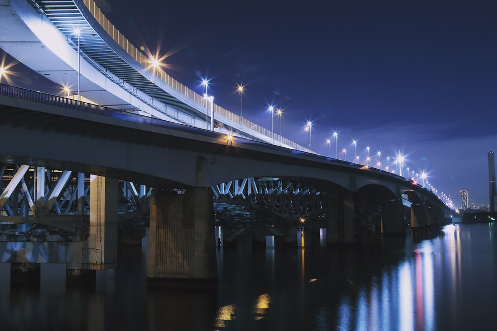 lighted bridge above calm body of water at night