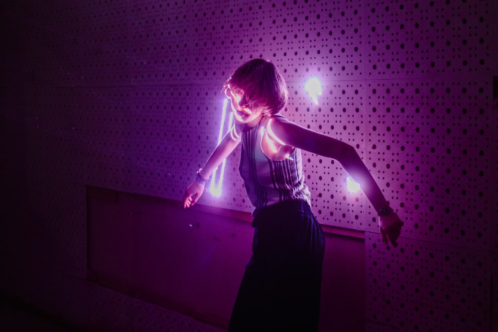 woman in grey tank top and black skirt leaning on wall with lighted pink bulbs