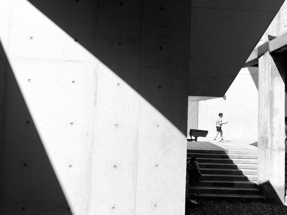 man walking past stairs in sidewalk grayscale photo