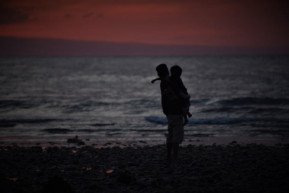 man carrying toddler on seashore