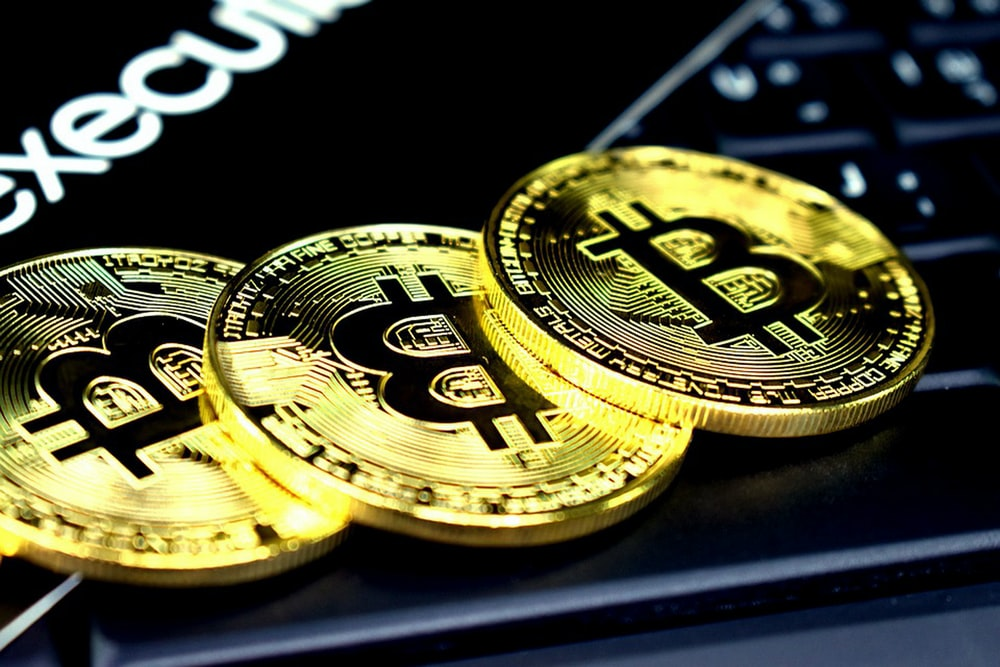 three round gold-colored bitcoins