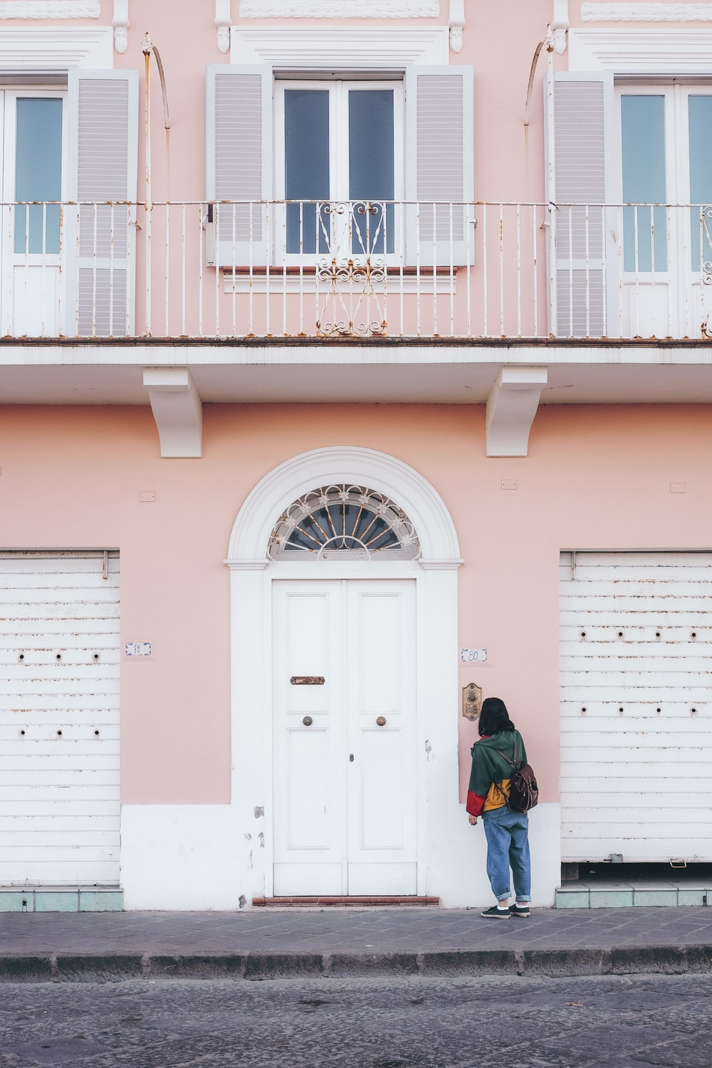 person standing in front of pink and white painted building