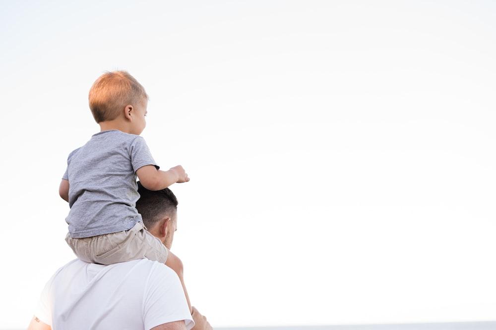 man in white shirt carrying boy