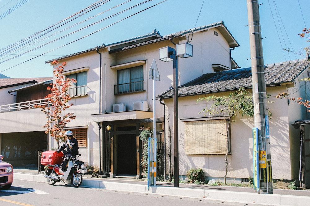 man standing beside house