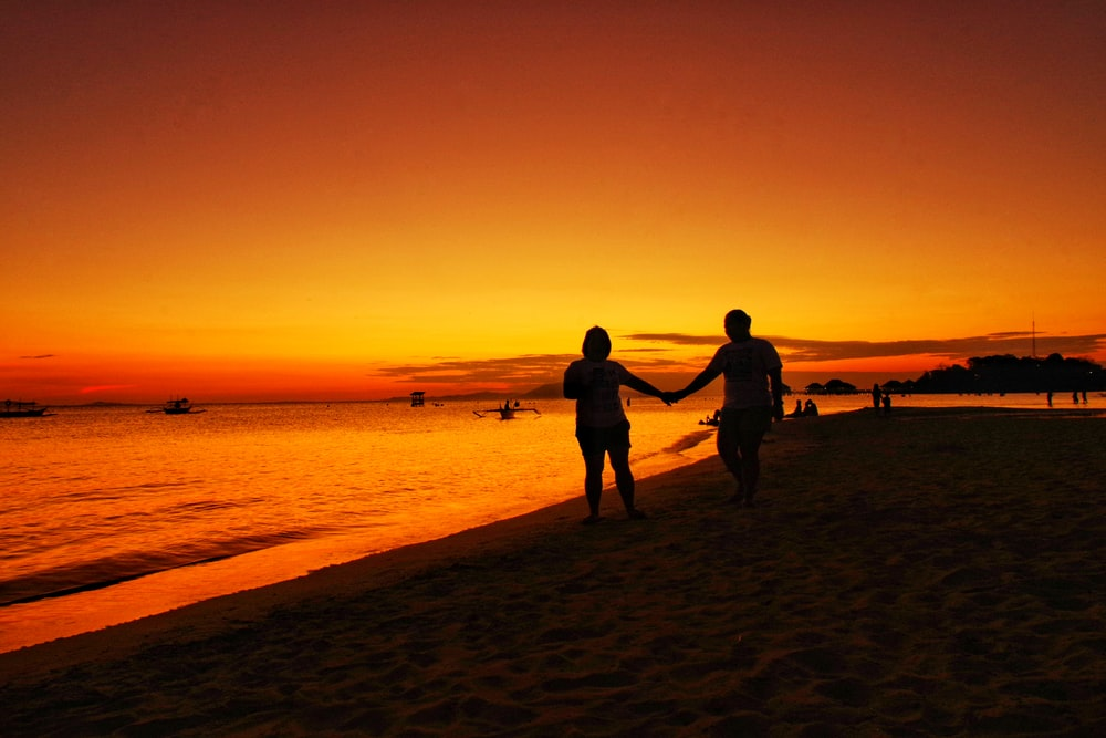man and woman walking hand in hand in beach at sunset