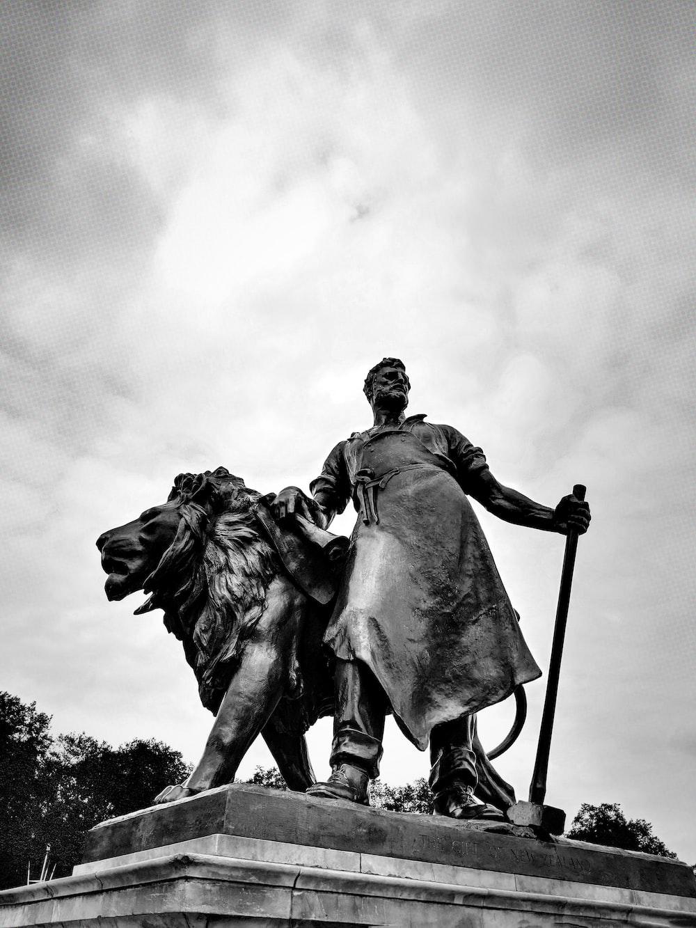 concrete man beside lion statue