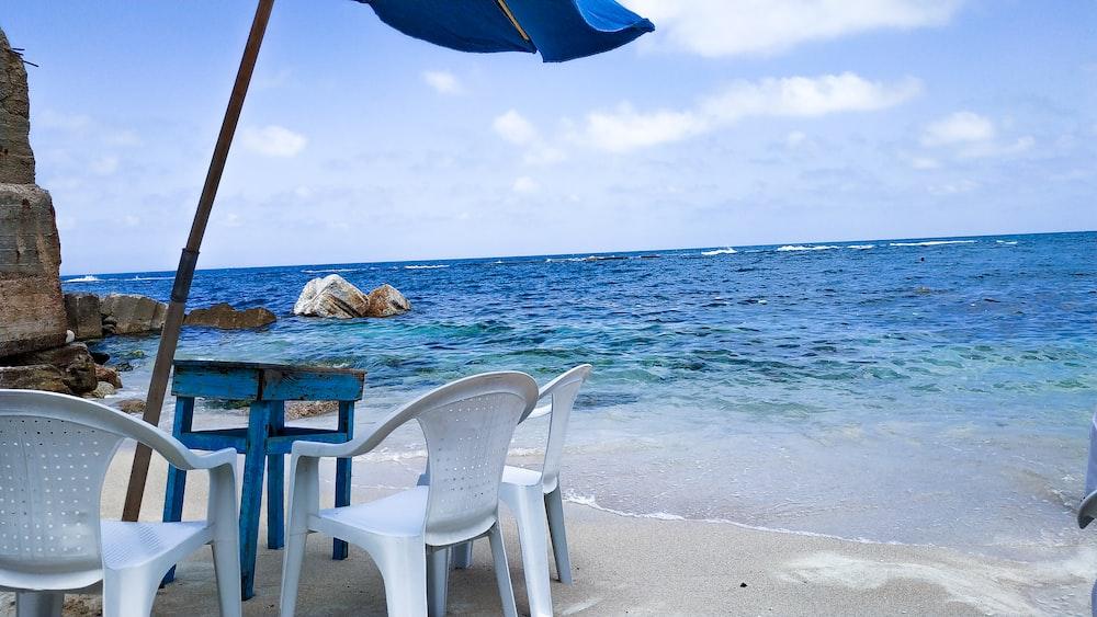 white monobloc armchairs beside sea