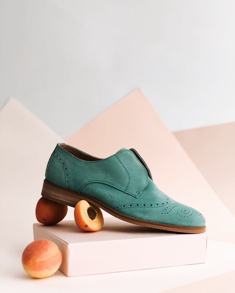 unpaired green leather shoe on top of white box