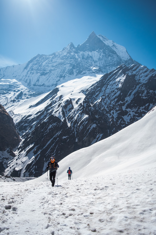 person holding ski sticks across white mountain