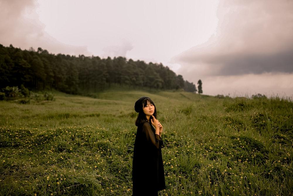 girl in black dress standing in green grass field