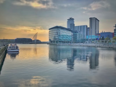 architectural photography of gray building near body of water manchester united zoom background