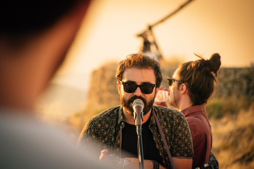 man wearing black sunglasses on microphone
