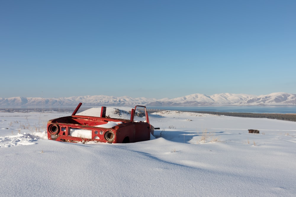 red wrecked car in the middle of ice surface