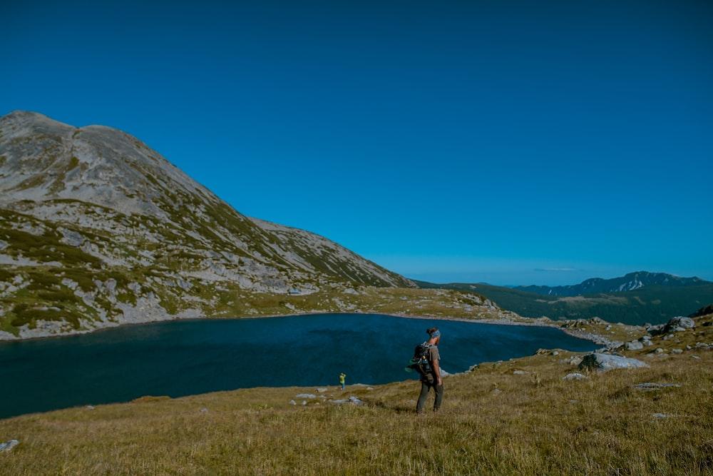 landscape photo of a man by a lake