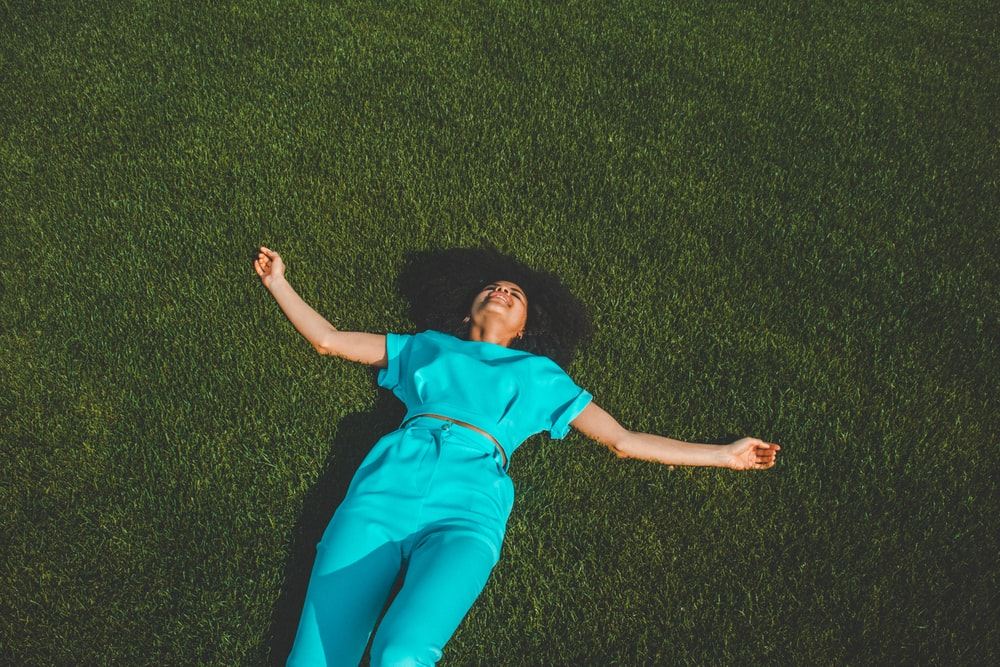woman wearing blue jumpsuit lying on green grass field