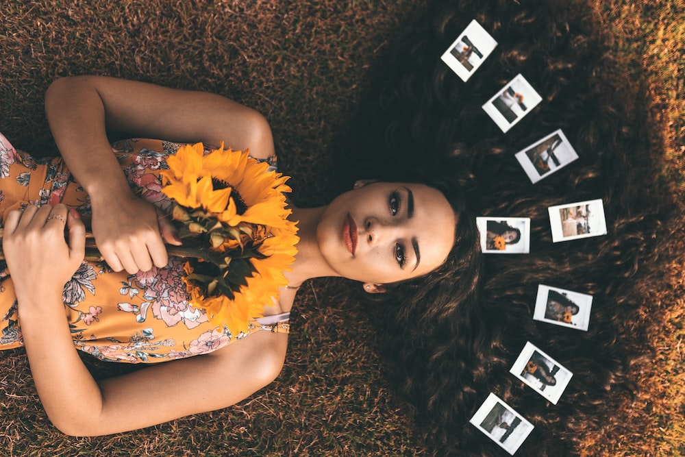 close-up photography of lying on woman on brown grass while holding sunflower
