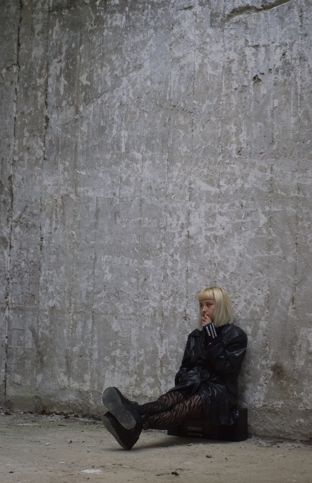 woman in black smoking by a gray wall