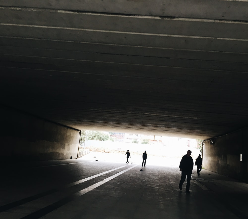 silhouette of person standing on tunnel