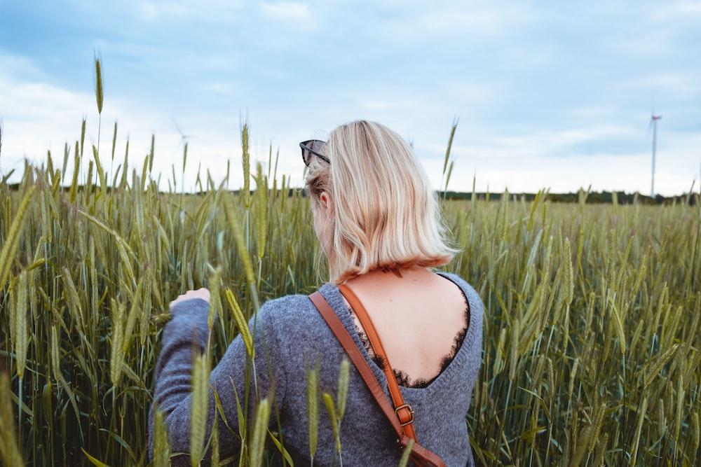 woman wearing gray long-sleeved shirt walking on grass field during daytime