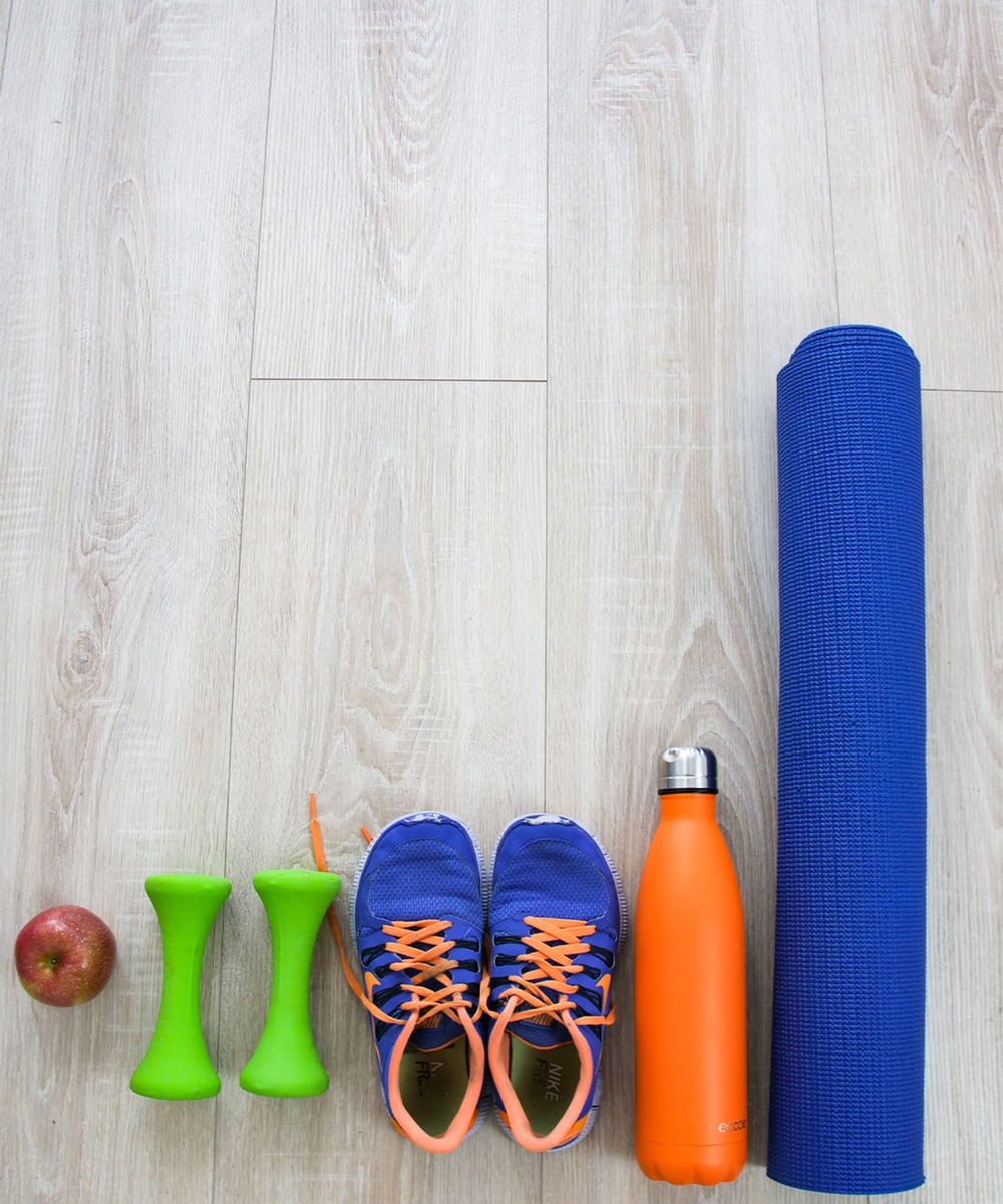 blue-and-orange running shoes and blue yoga mat