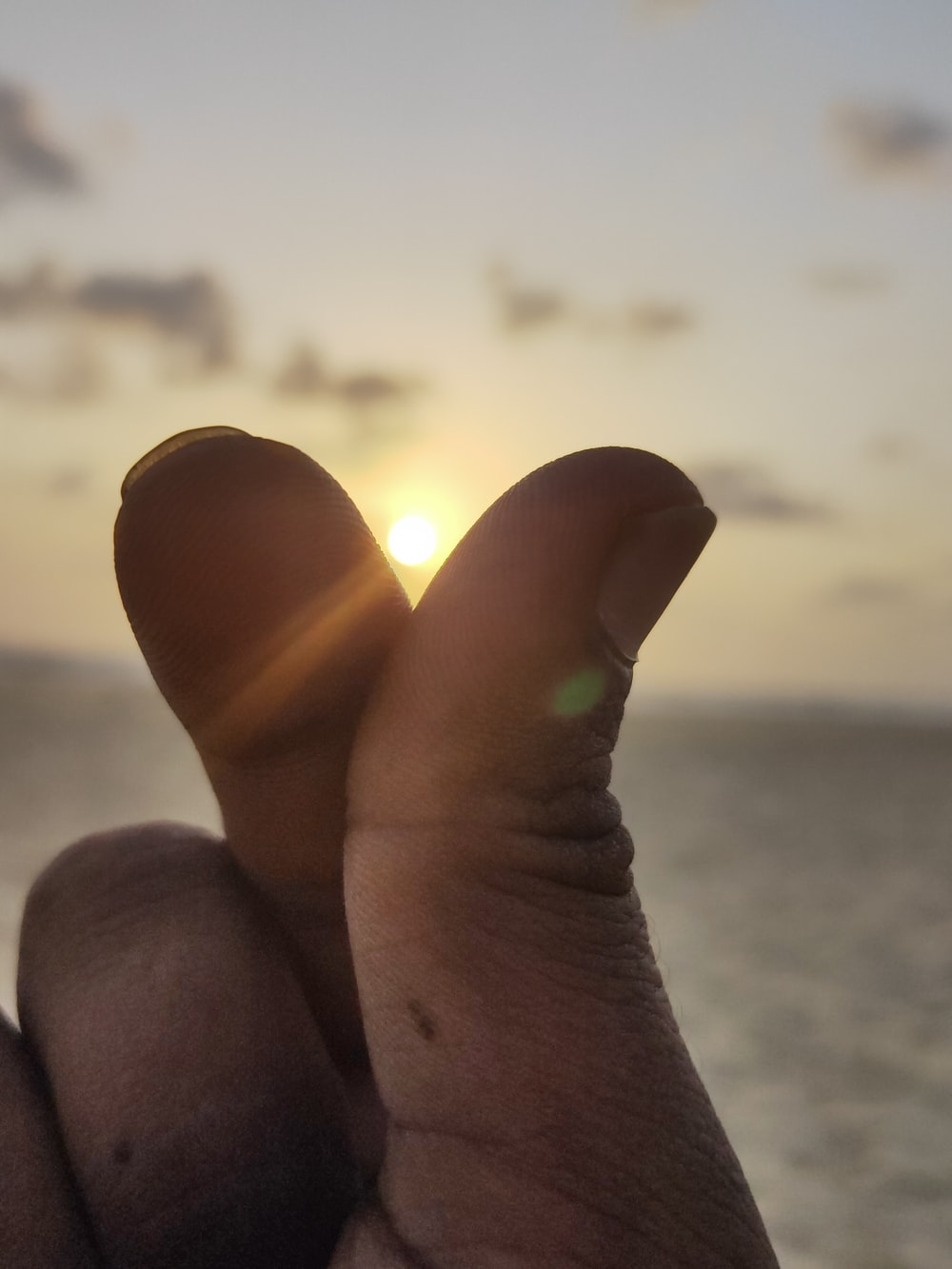 person's right hand at sunset