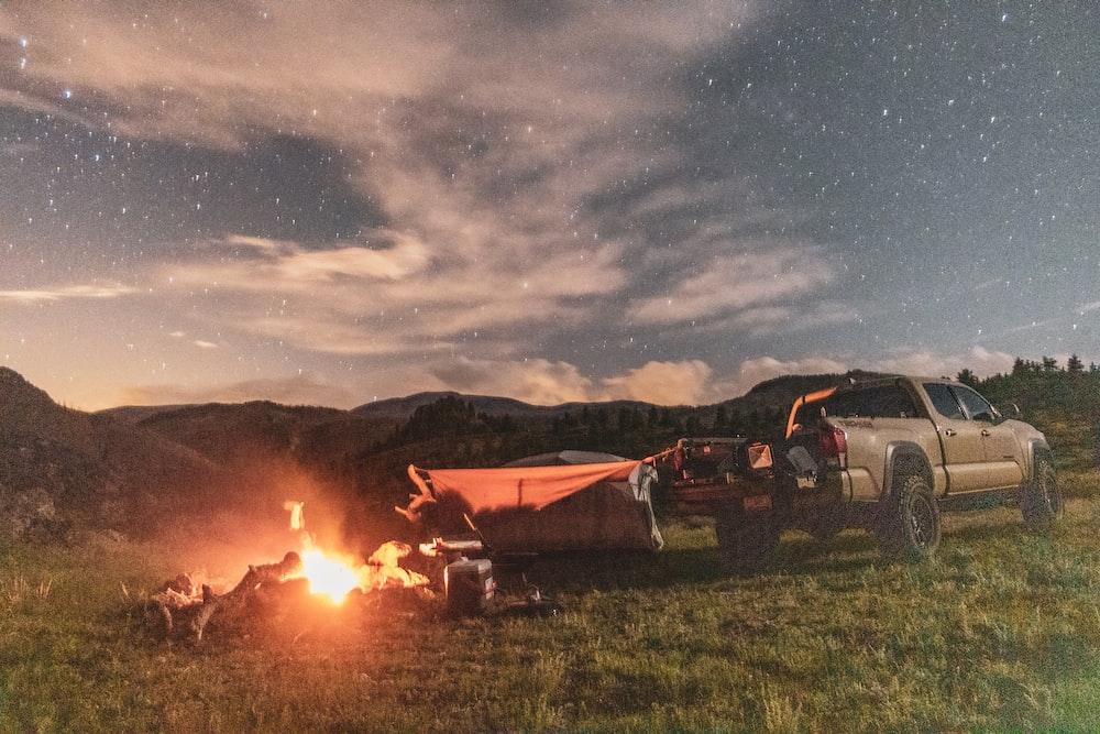 brown pickup truck beside brown camping tent