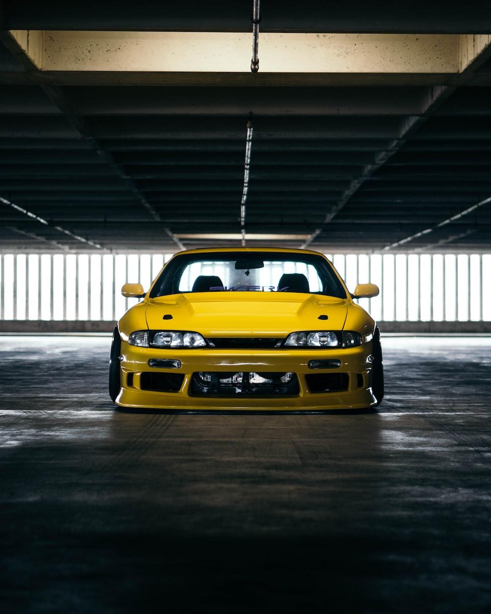 yellow sports car parking inside garage