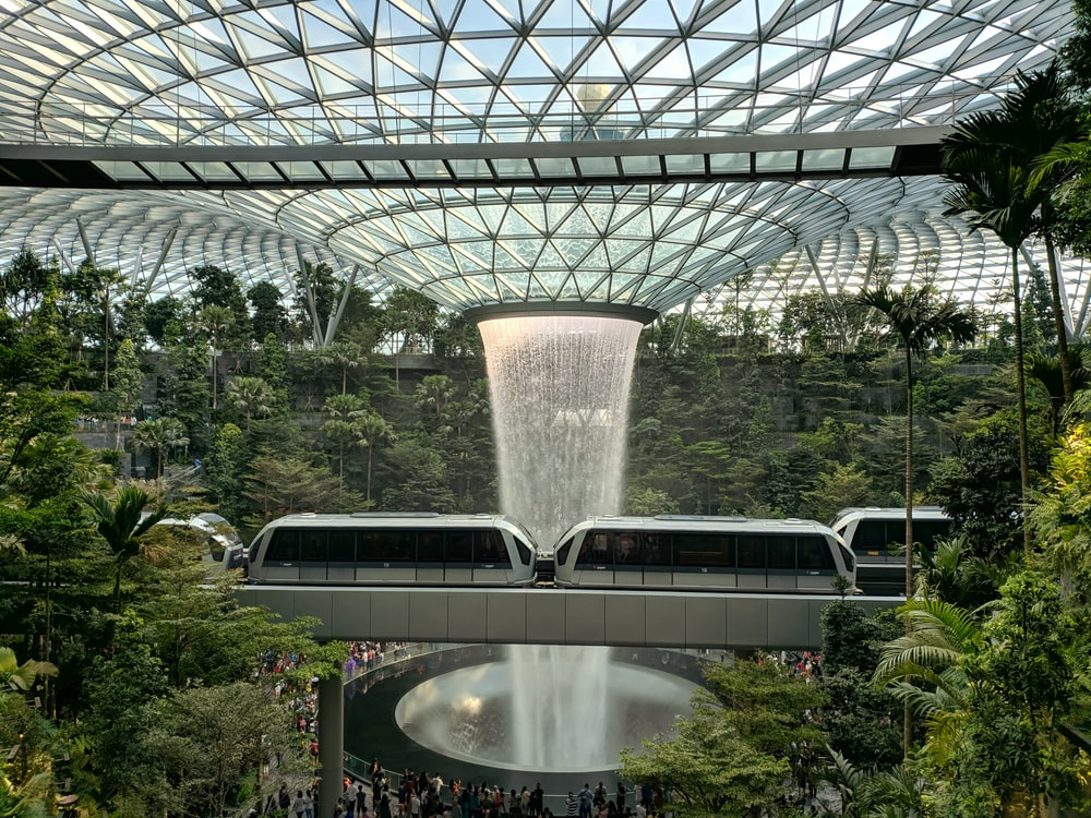 train near trees inside building with indoor waterfalls