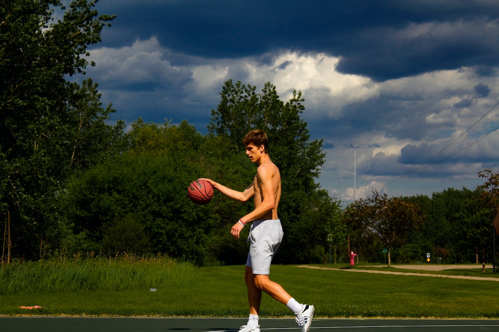 topless man holding basketball during daytime